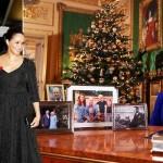エリザベス女王はテーブルの後ろに座っており、王室の4人の額入り写真がテーブルに置かれています。